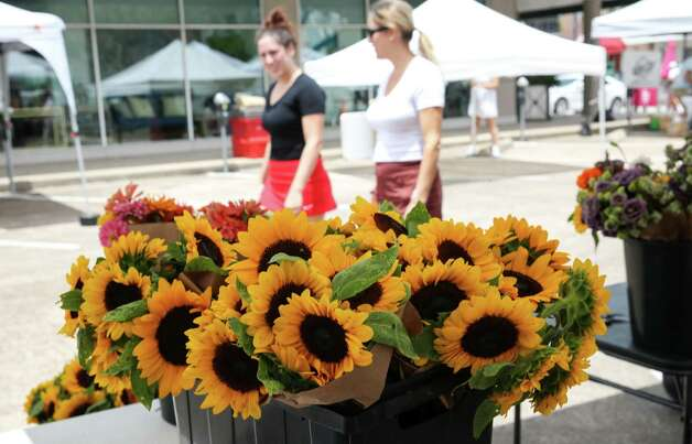 People walk by flowers for sale from Addy's Flower Farm on Sunday, June 20, 2021, at the Rice Village Farmers Market in Houston. Photo: Jon Shapley, Houston Chronicle / Staff Photographer / © 2021 Houston Chronicle