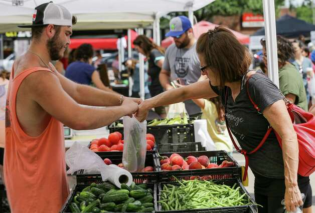 Logan Alexander, who works at Theiss Market, helps a customer during the Tomball Farmers Market -which is located at 205 West Main Street - on Saturday, June 12, 2021, in Tomball Photo: Godofredo A. Vásquez, Houston Chronicle / Staff Photographer / © 2021 Houston Chronicle