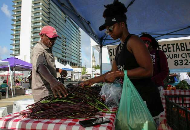 Crysta Parker selects produce sold by Ely Ngou, left, at the Sustainable Vegetabe Garden tent at the Urban Harvest Farmers Market. Photo: Godofredo A. Vásquez, Houston Chronicle / Staff Photographer / © 2021 Houston Chronicle