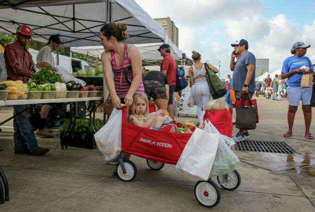 Elise Lorensen hangs a bag of produce to a four-wheel cart while shopping at Urban Harvest Farmers Market - which is located at 2752 Buffalo Speedway - with her children Mia and Blake on Saturday, June 12, 2021, in Houston. Photo: Godofredo A. Vásquez, Houston Chronicle / Staff Photographer / © 2021 Houston Chronicle