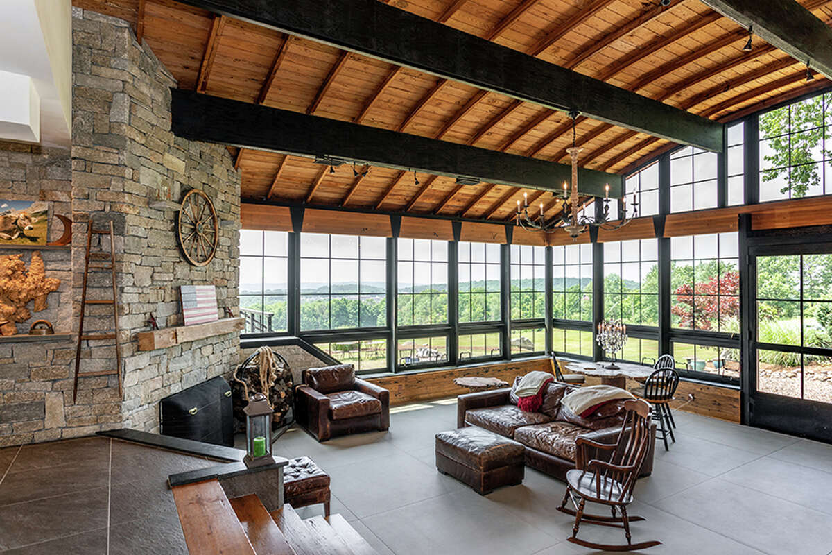 The living roomhas floor-to-ceiling windows on two sides, a fireplace and exposed beams. View listing