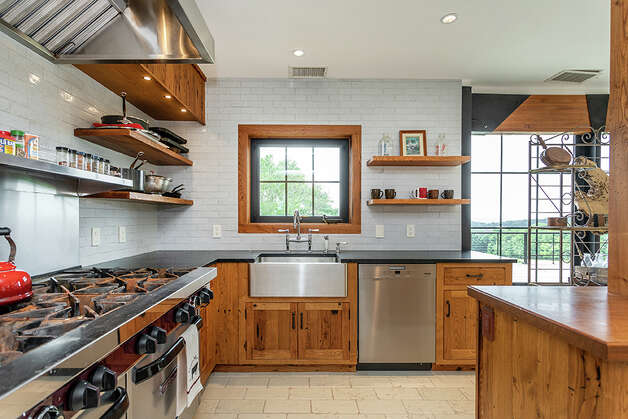 The kitchenis outfitted with a 10-burner double range and a farmhouse-style sink. View listing Photo: Michael Bowman / Michael Bowman Photography