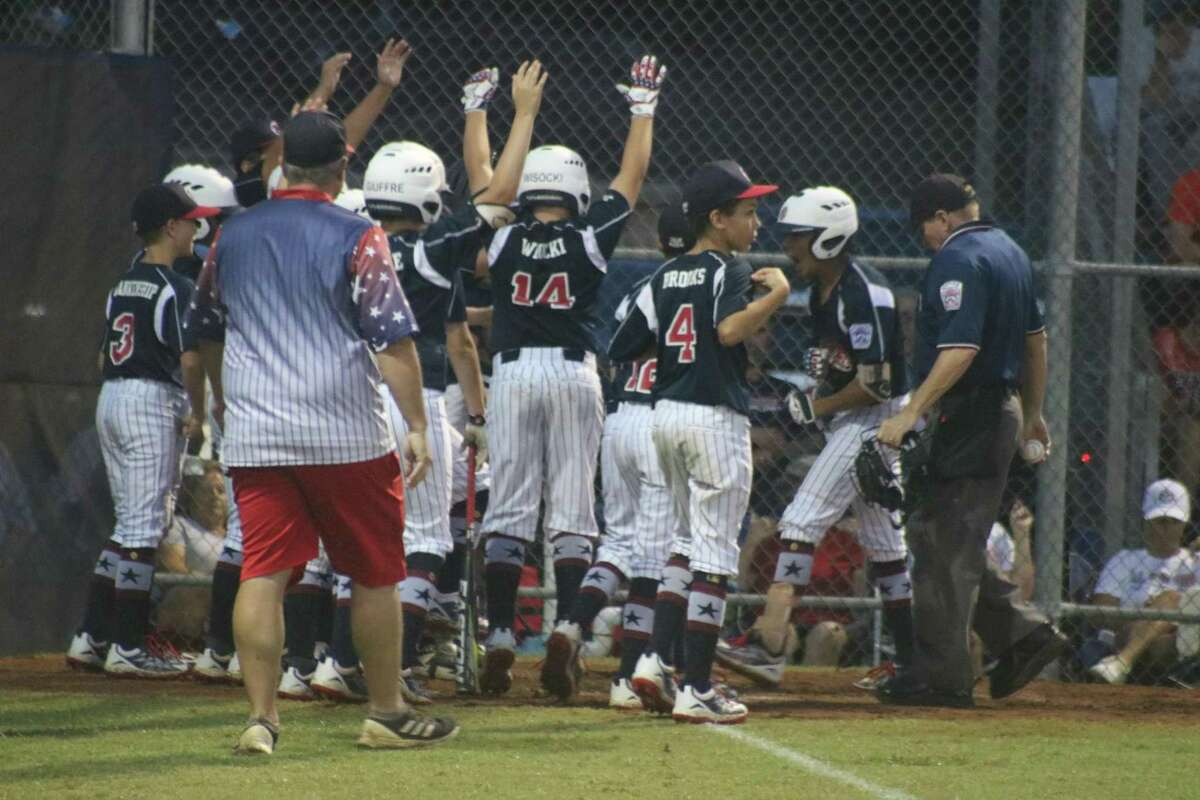 An excited group of NASA Major all-stars greet Kaled Fadoa at home plate after he belted a solo home run in the first inning Monday night. It would be the team's only RBI of the game. It's his second homer in as many nights.