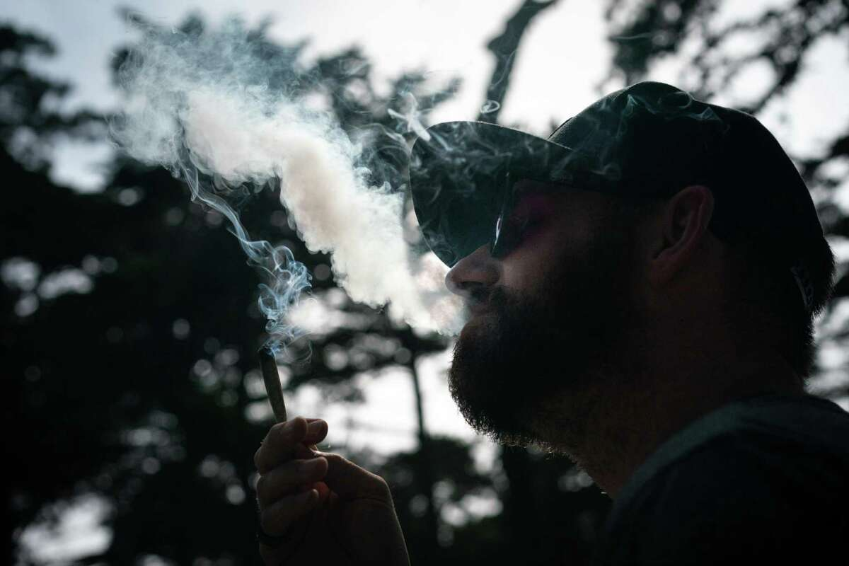 Adam Headman smokes a joint at Outside Lands on Saturday, Aug. 10, 2019, in San Francisco, Calif.