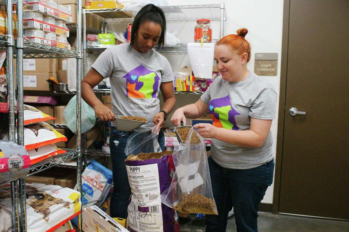 League City Animal Care's animal services manager, Jasmine O'Keefe, left, and community outreach/volunteer coordinator Lynette Bodmer bag puppy food to distribute through the shelter's pantry. To aid struggling pet owners, the shelter will host its next monthly Pet Pantry Drive Thru food and supply distribution event July 11 from 8-10 a.m. or for as long as supplies last.