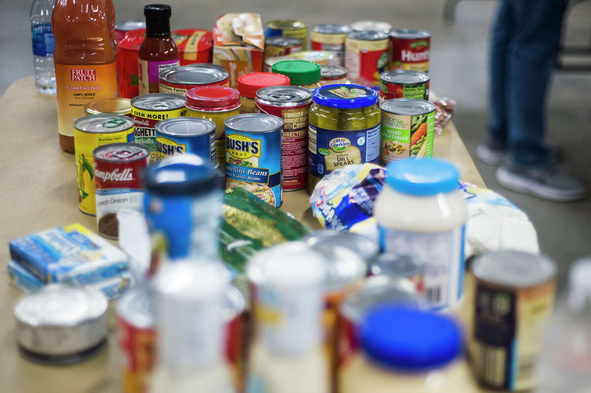 Volunteers work to organize donated food items, which were collected through the United Way's Summer Stock Up food drive, Tuesday, June 29, 2021 at Dow Diamond. The donated items will be distributed by Hidden Harvest to food pantries throughout the region. (Katy Kildee/kkildee@mdn.net)