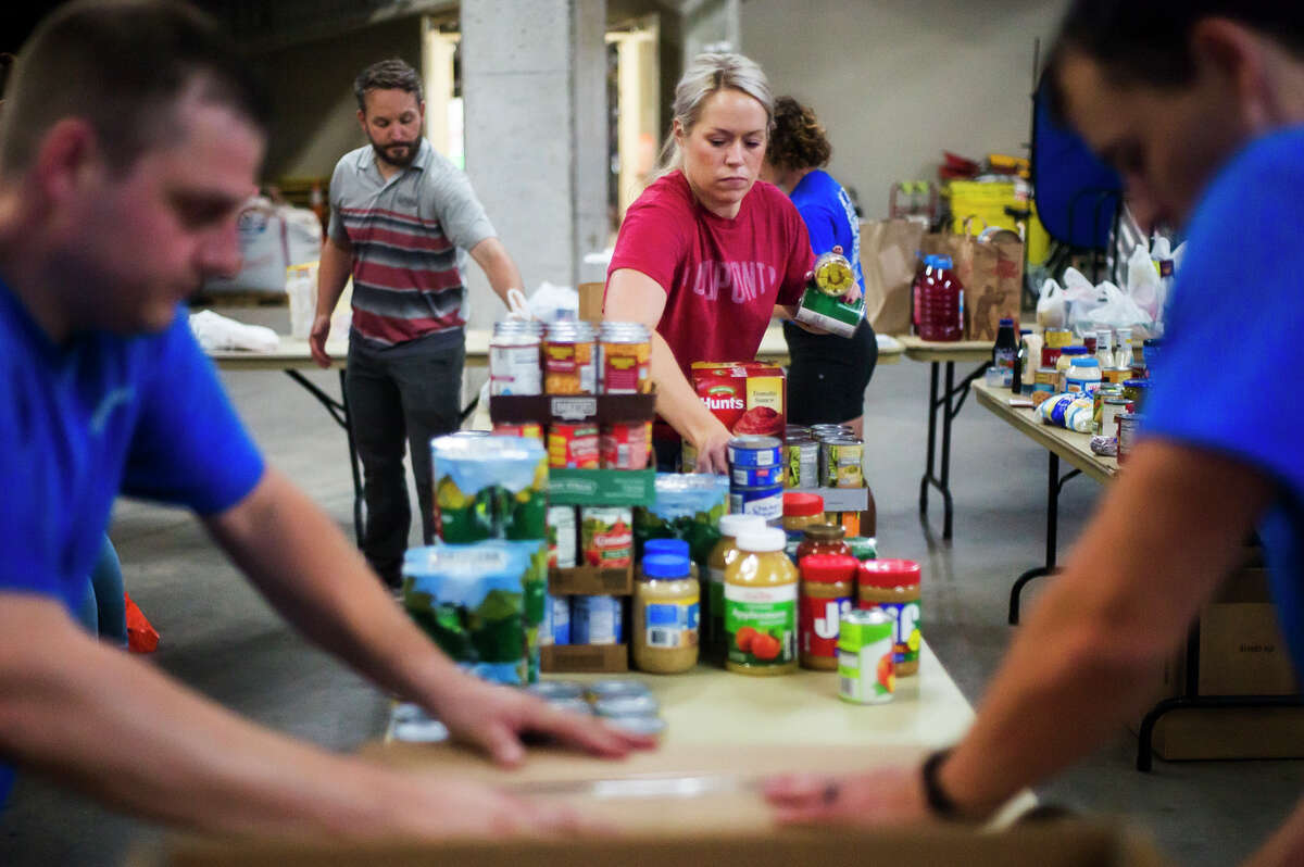 Kayley Lyons, community relations leader at DuPont Performance Building Solutions, center, works to organize donated food items, which were collected through the United Way's Summer Stock Up food drive, Tuesday, June 29, 2021 at Dow Diamond. The donated items will be distributed by Hidden Harvest to food pantries throughout the region. (Katy Kildee/kkildee@mdn.net)