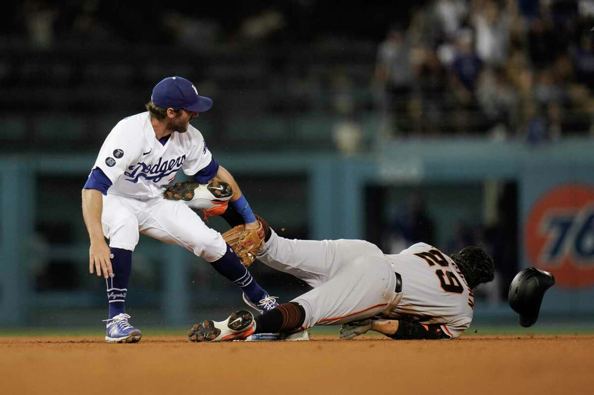Los Angeles Dodgers' Chris Taylor, left, tags out San Francisco Giants' Mike Tauchman as Tauchman tries to take second base after hitting a single during the ninth inning of a baseball game, Monday, June 28, 2021, in Los Angeles. (AP Photo/Jae C. Hong)