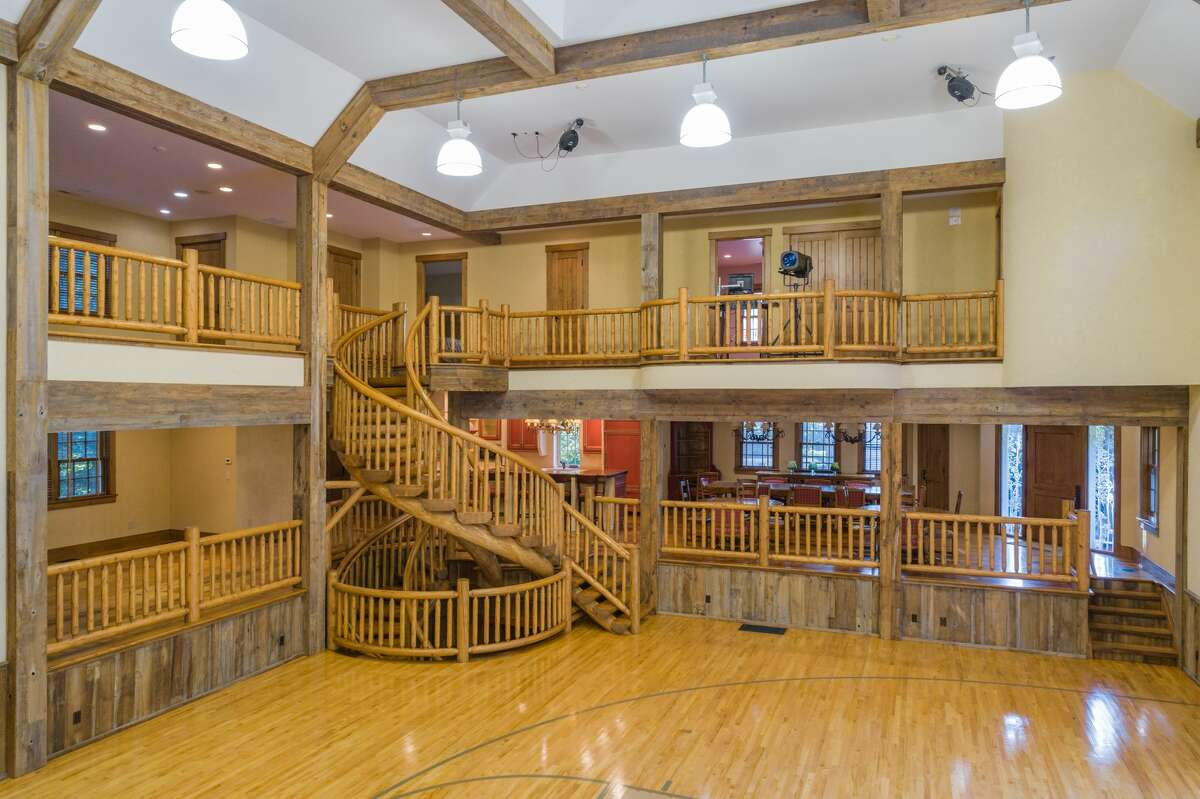 """Inside the """"sports barn"""" on the 364 Laurel Road property in New Canaan, Conn., there is a basketball court, movie theater, dining area and recreation space."""