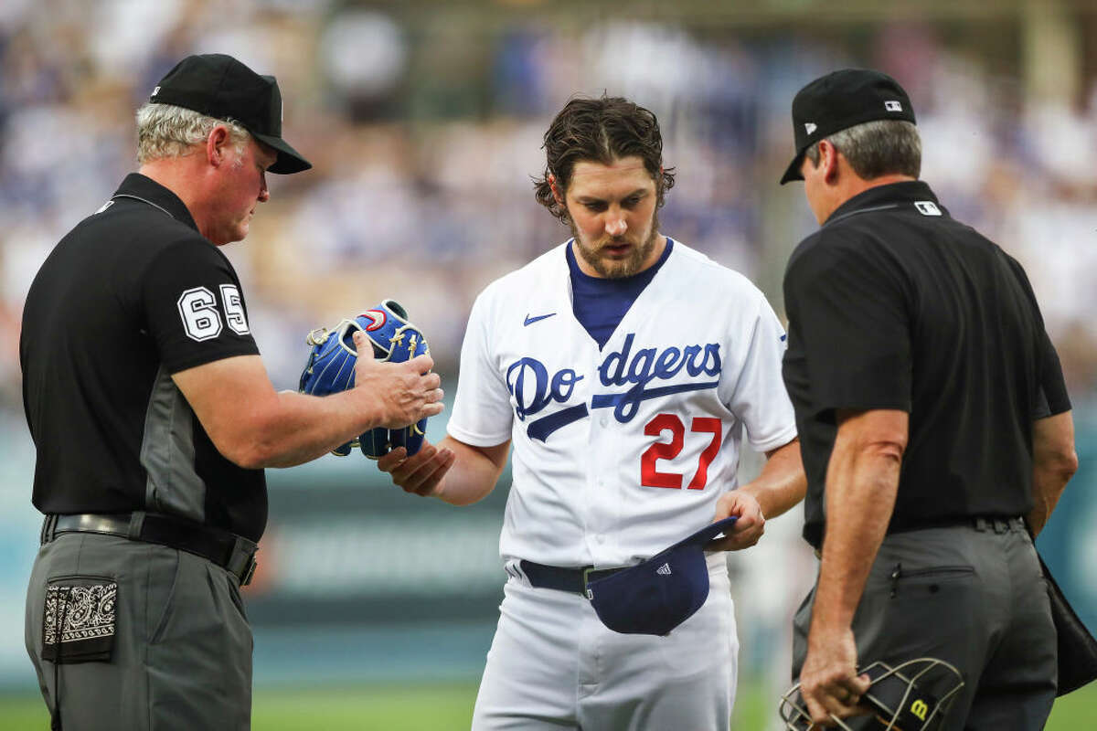 Umpires check the hat and glove of Trevor Bauer of the Los Angeles Dodgers for foreign substances after the first inning against the San Francisco Giants at Dodger Stadium on June 28, 2021.