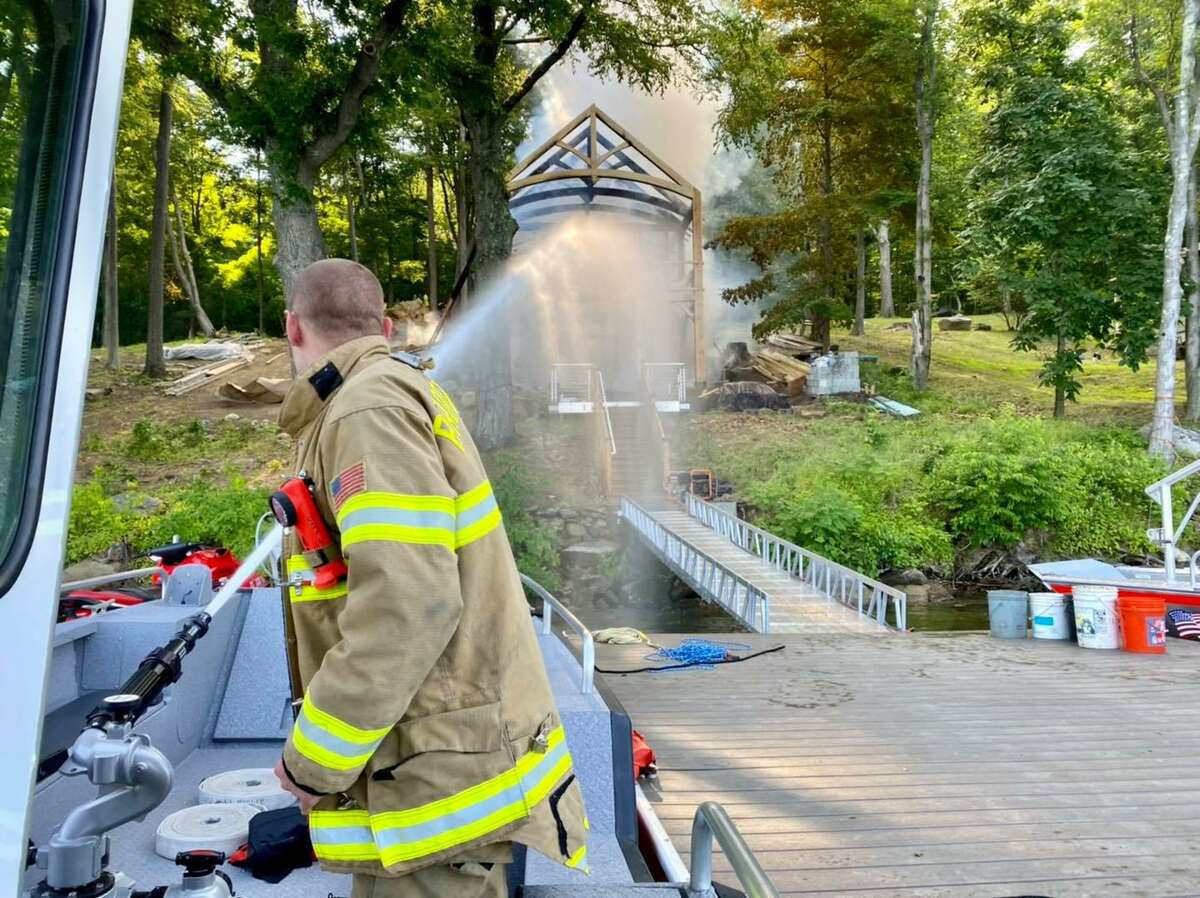 Firefighters douse water on a lakefront structure that caught fire in New Fairfield, Conn., the morning of June 29, 2021.
