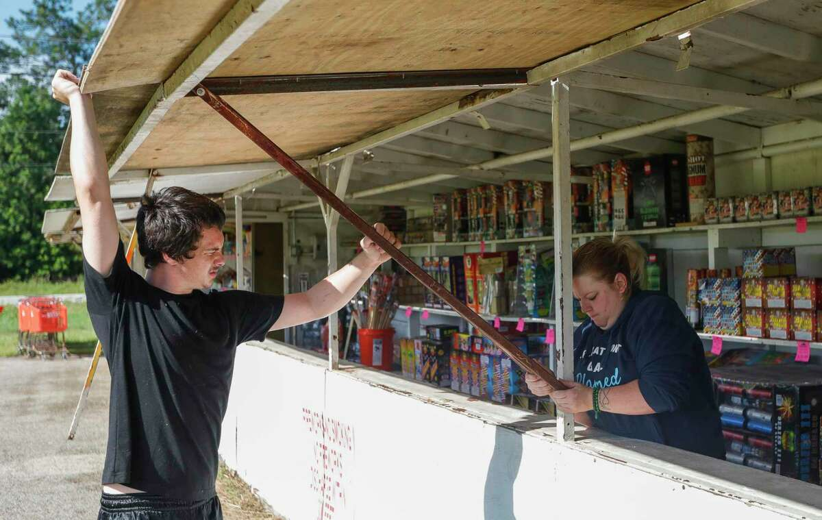Terri Valencia helps Katherine Lapole open up a fireworks stand for customers at Magnum Fireworks along FM 2854 near McCaleb Road, Tuesday, June 29, 2021, in Conroe.