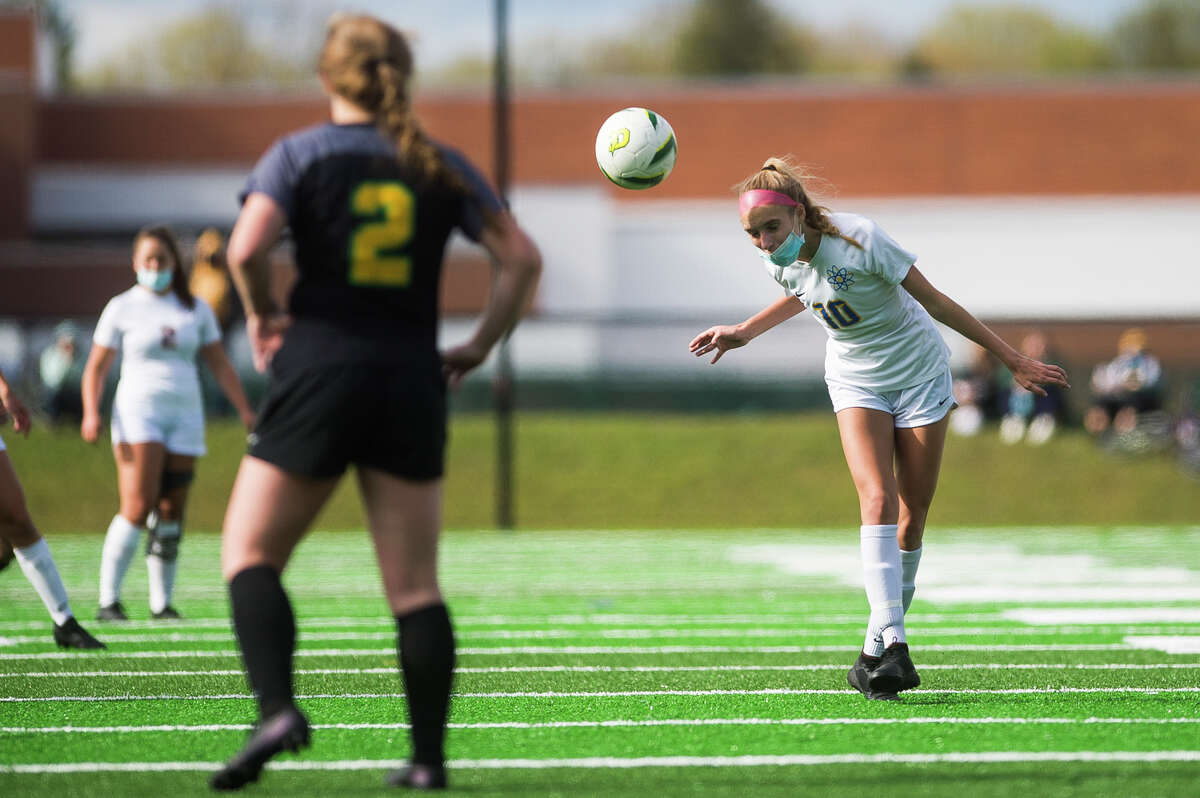 Midland High's Chloe Rajewski heads the ball during a May 10, 2021 game against Dow High.