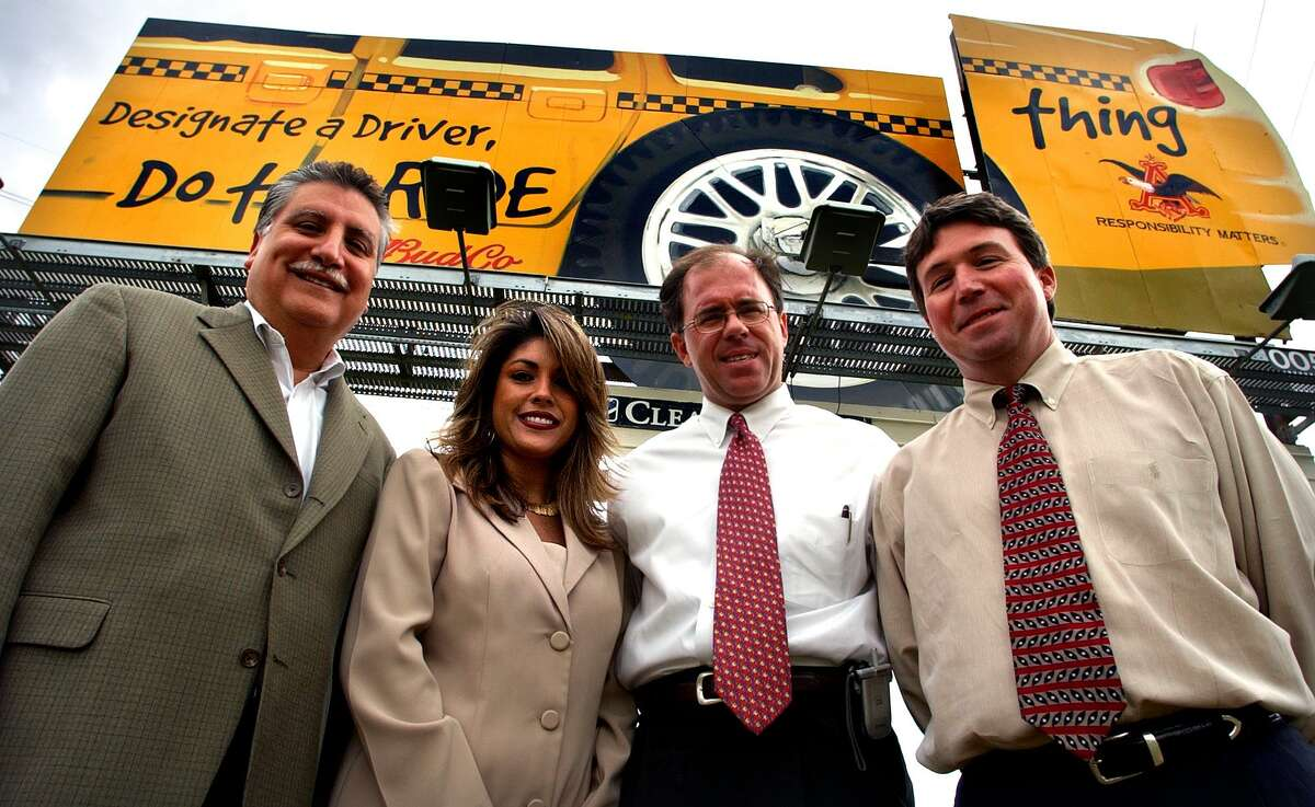 In this 2004 photo, J.J. Amaro, left to right, and Cecelia Reagan, of BudCo, stand with Chris Murphy and Danny Berry of Clear Channel Outdoor in front of what is known as the old ButterKrust mechanical billboard.