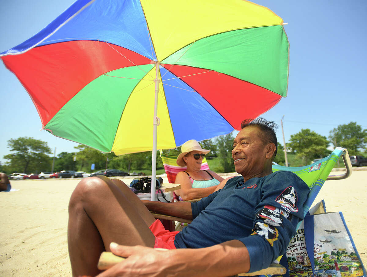 Rolando and Marianne Tecun, of Bridgeport, beat the heat with their first trip to the beach of the summer at Seaside Park in Bridgeport, Conn. on Tuesday, June 29, 2021.