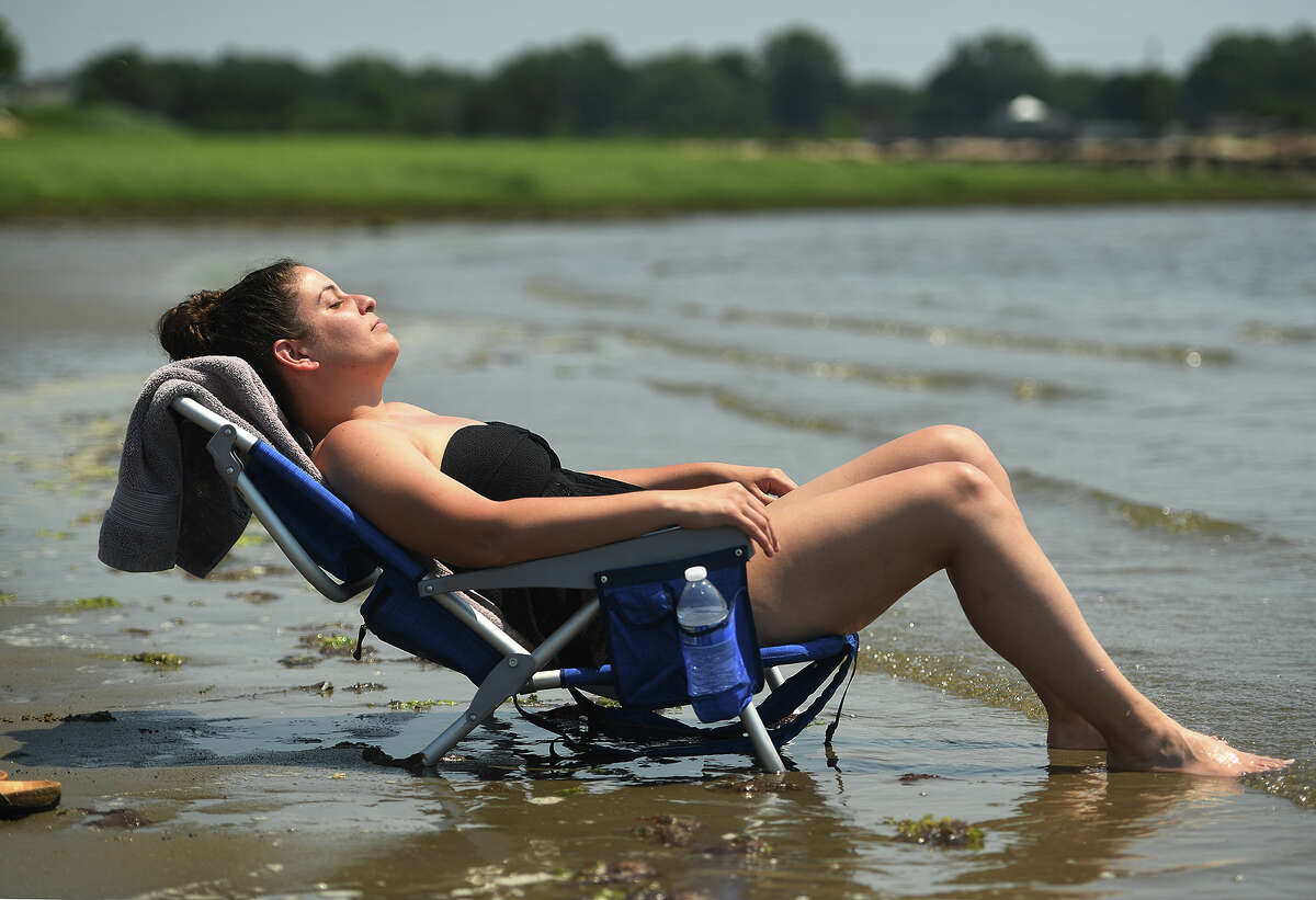 Stacey Krasnoff, of Milford, beats the heat with her feet in the lapping water of the Sound at Fort Trumbull Beach in Milford, Conn. on Tuesday, June 29, 2021.