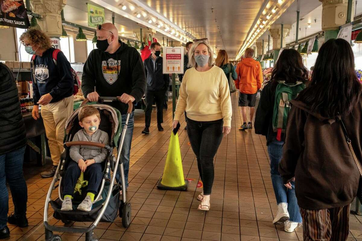 People walk through Pike Place Market as Seattle has become the first major city to reach a 70 percent COVID-19 vaccination rate on June 10, 2021 in Seattle, Washington.
