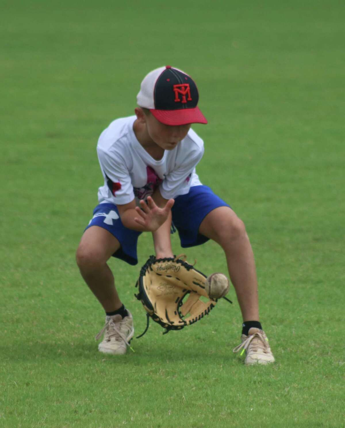 Randy Weaver fields a ground ball during the Deer Park baseball camp last week. The fielding seems to be the easy part. The coaches worked with the kids on the harder part, making accurate throws to their intended target.