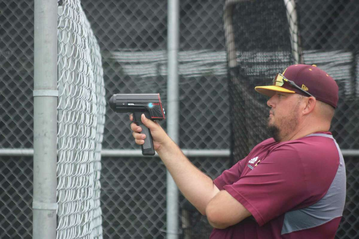 Deer Park assistant baseball coach Justin Garney checks the velocity of pitches from the youngsters during the program's camp last Thursday.