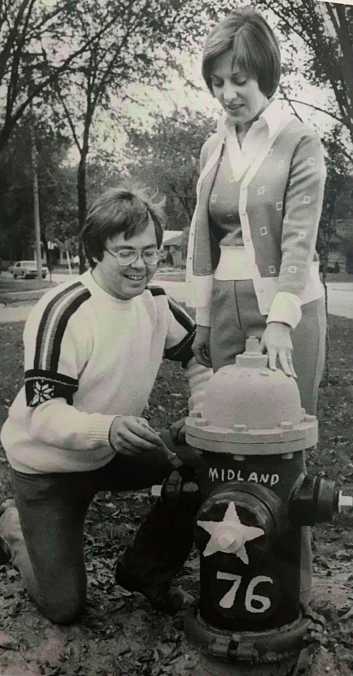 Stephen J. Engelken, administrative assistant for the Midland Community Affairs Council, paints the first hydrant in advance of the Bicentennial Fire Hydrant Painting Contest sponsored by Women's Optimist League. Looking on is Leslie Causgrove, head of the league. October 1975