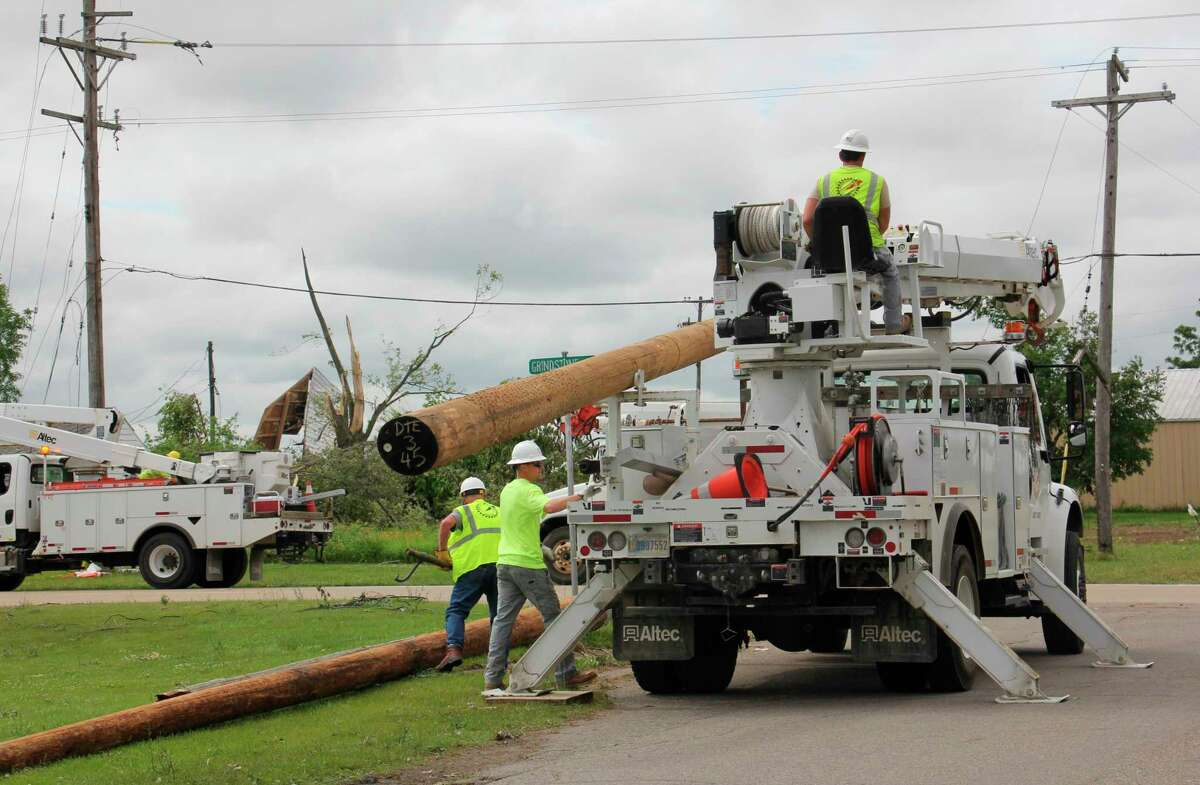 DTE lineworkers hoist a beam for a power line up on Grindstone Road June 28. (Teresa Homsi / Huron Daily Tribune)
