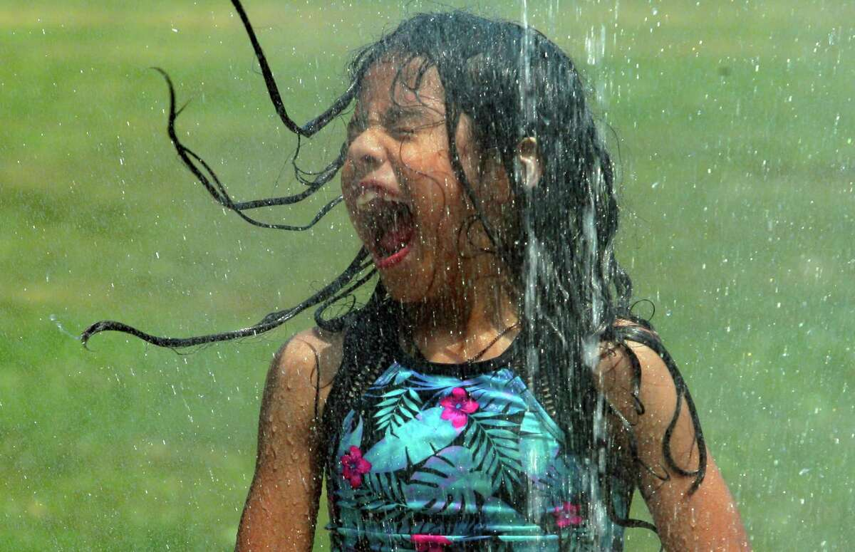 Above, Skylar Culqui, 8, of Stamford, screams as she spins around in the water from the splash pad at Scalzi Park in Stamford, on June 18, 2021.