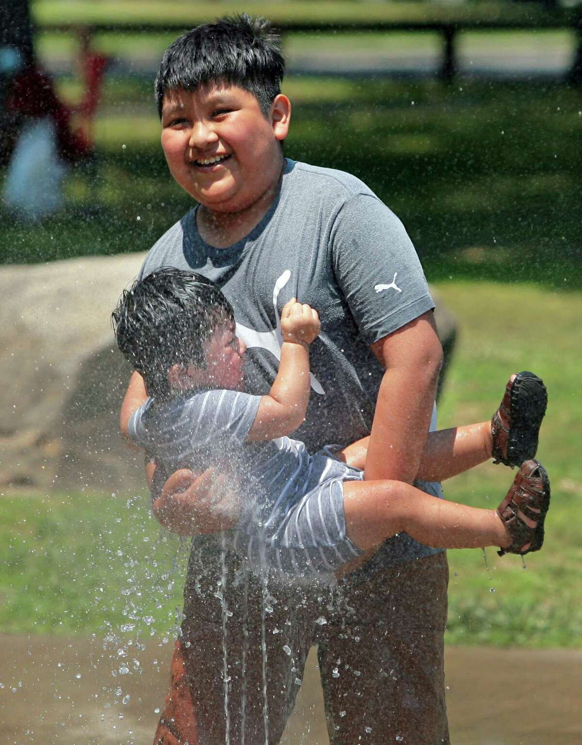 Selvin Castillo, 10, holds his baby brother Leon, 1, in the water from the splash pad at Scalzi Park.in Stamford, Conn., on Friday June 18, 2021.