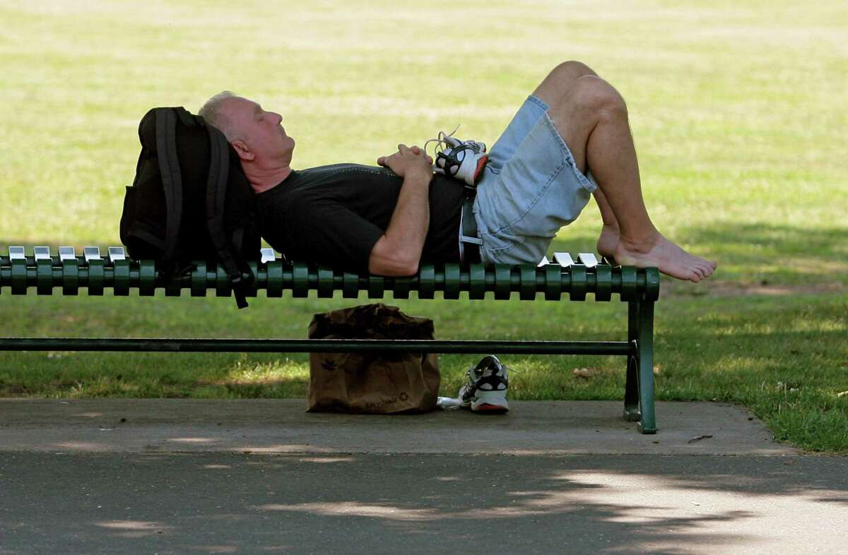 Paul, of Stamford, beats the heat by resting on a bench in the shade at Scalzi Park.in Stamford, Conn., on Friday June 18, 2021.
