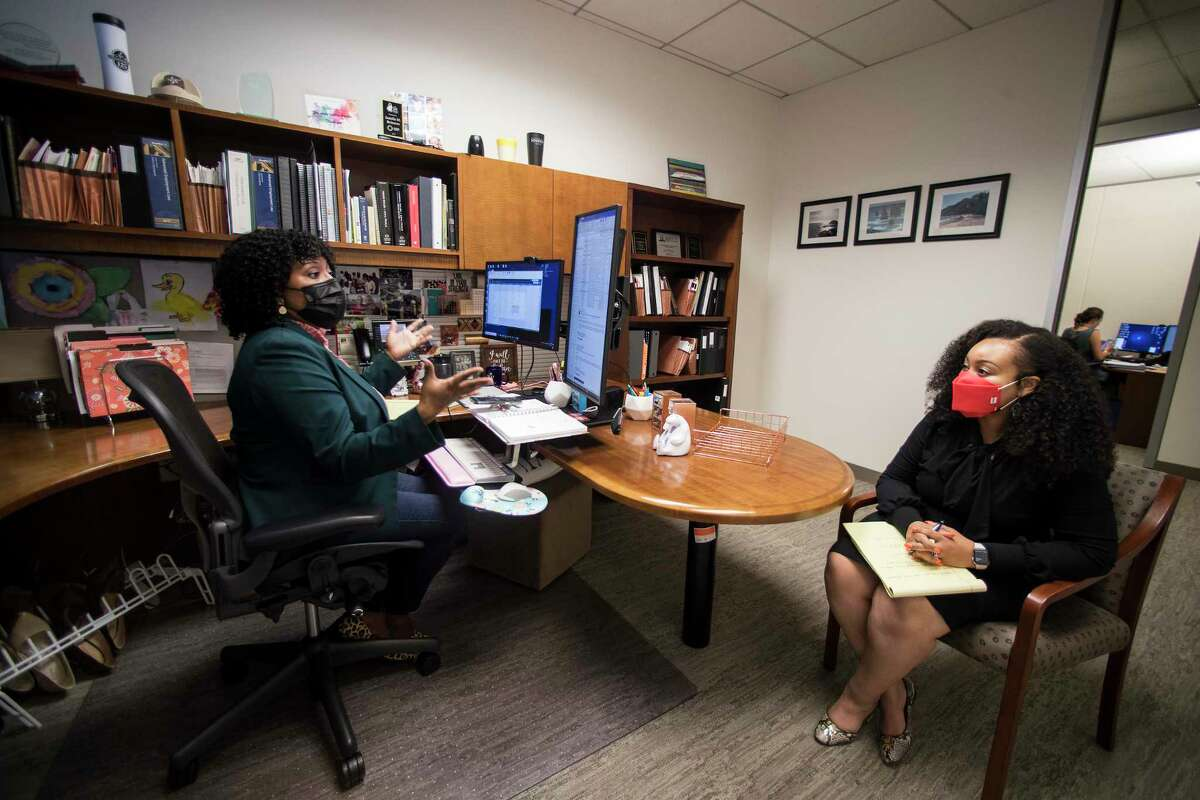 Attorneys Jamila Brinson, left, and Dawn Holiday meet in Brinson's office at the Jackson Walker law firm, where they are both partners, Thursday, May 20, 2021 in Houston. Jackson Walker brought employees back to their Downtown office for the first time this week, days after the Centers for Disease Control and White House announced new guidelines for mask-wearing and social-distancing for vaccinated people.
