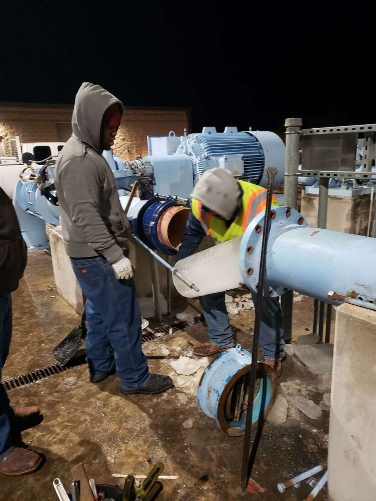 """Frederick Williams and Brandon Banda, SAWS workers, pull an """"ice slug"""" Thursday night from a pump station in 7800 block of Huermann Road. The water inside the pump froze after CPS Energy cut power to the station."""