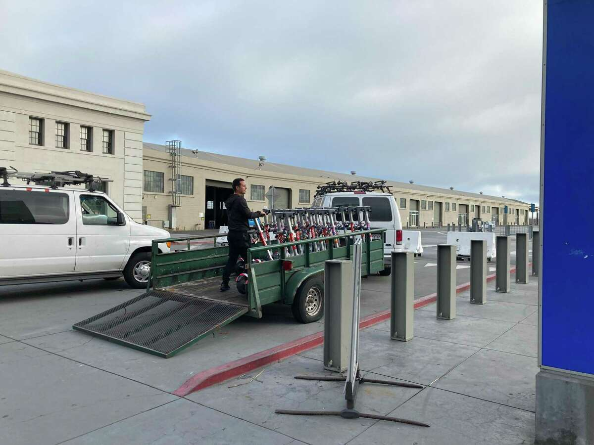 A Scoot worker checks scooters at Pier 27 in San Francisco, in a photo from 2020.