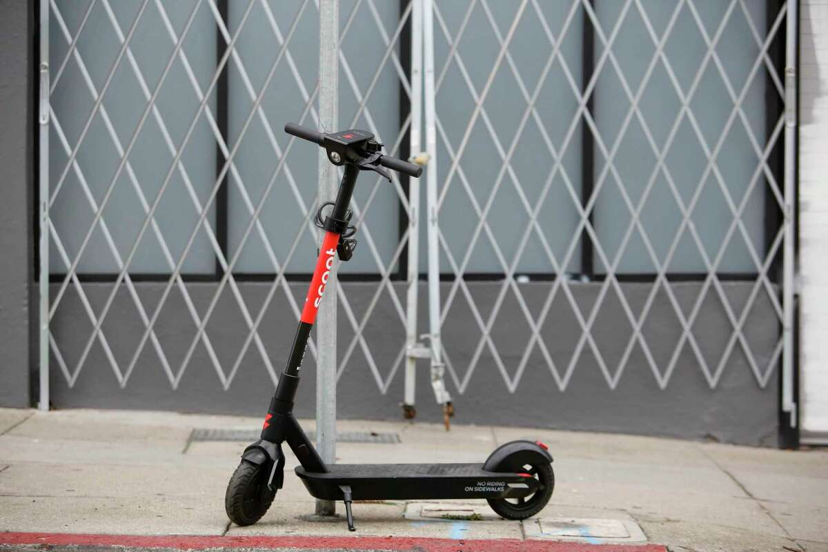 A Scoot scooter deployed in October is seen locked on sign post in San Francisco. The company has been ordered to stop operations in the city after violating permit agreements.