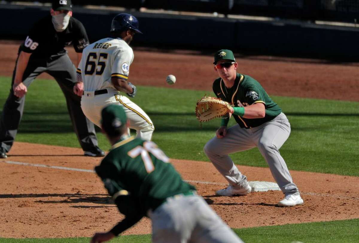 Brian Howard throws to first baseman Frank Schwindel on a spring training pickoff attempt in Arizona. Schwindel was called up to the A's Tuesday.