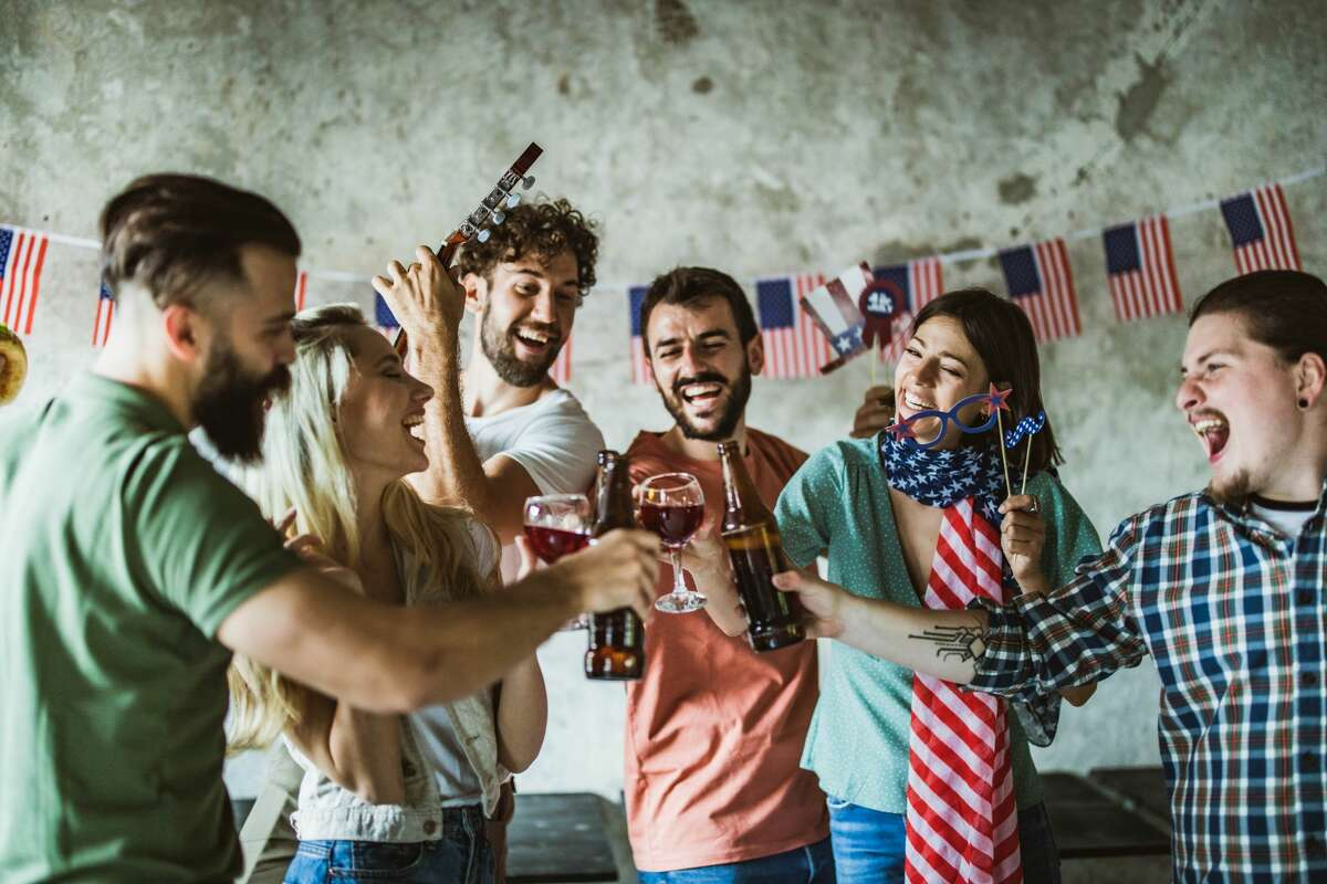 Millennial friends having fun at casual office while toasting with alcohol during Independence day.