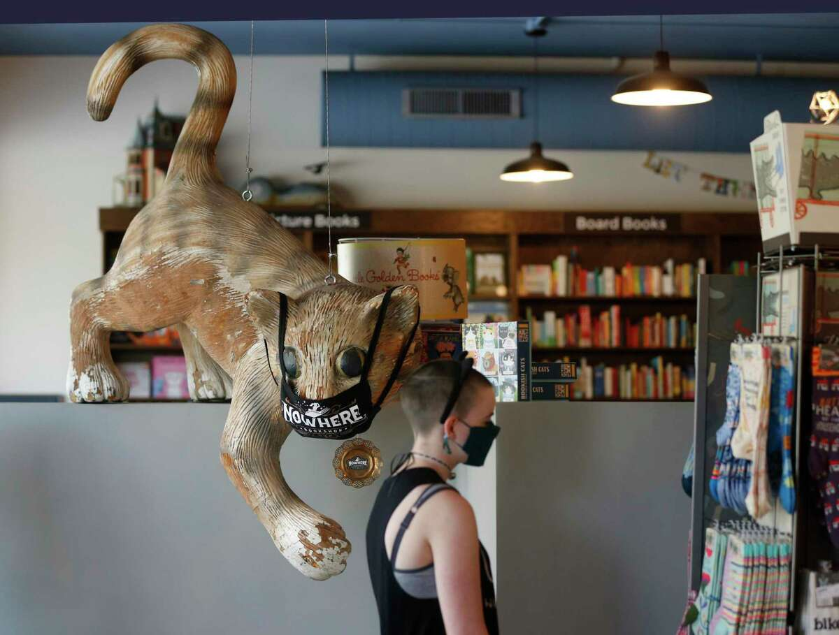 A giant cat looms over Nora Lowry as she checks out the books at Nowhere Bookshop in Alamo Heights, recently. The store's decor reflect the off-kilter sense of humor of the shop's owner and best-selling author, Jenny Lawson.
