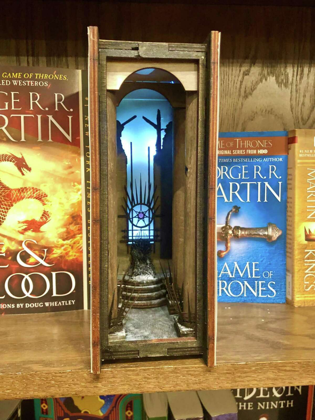 """A number of narrow illuminated dioramas called book nooks are hidden in plain site on shelves throughout Nowhere Bookshop. Each has a different literary theme, including Calvin and Hobbes, """"The Chronicles of Narnia"""" and, pictured, """"Game of Thrones."""""""