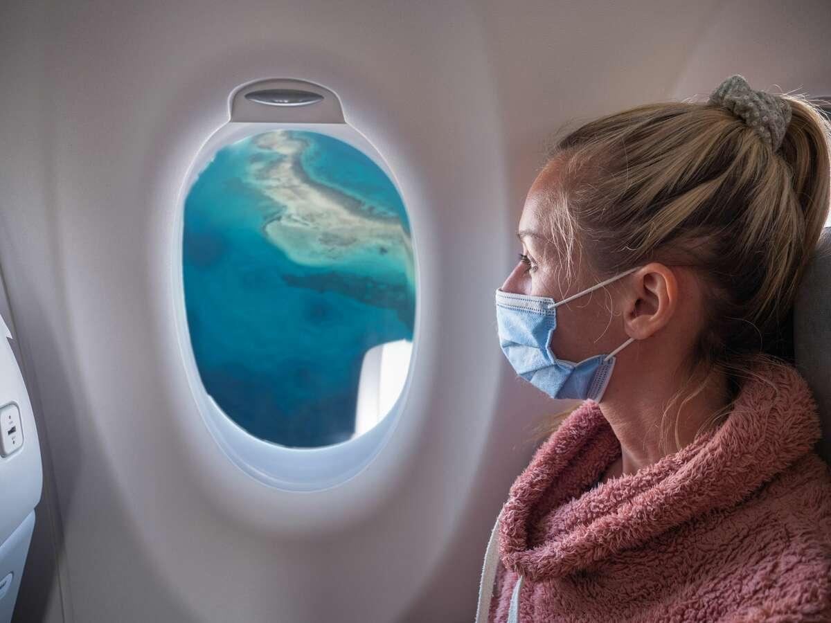 Woman sitting inside airplane enjoying flight. Tourist wearing facial mask due to Covid-19 crises