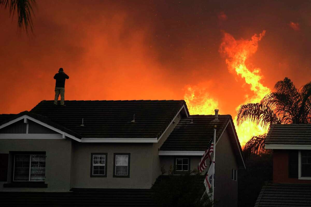 Herman Termeer, 54, stands on the roof of his home as the Blue Ridge Fire burns along the hillside Tuesday, Oct. 27, 2020, in Chino Hills, Calif. Facing extreme wildfire conditions this week that included hurricane-level winds, the main utility in Northern California cut power to nearly 1 million people while its counterpart in Southern California pulled the plug on just 30 customers to prevent power lines and other electrical equipment from sparking a blaze.(AP Photo/Jae C. Hong)