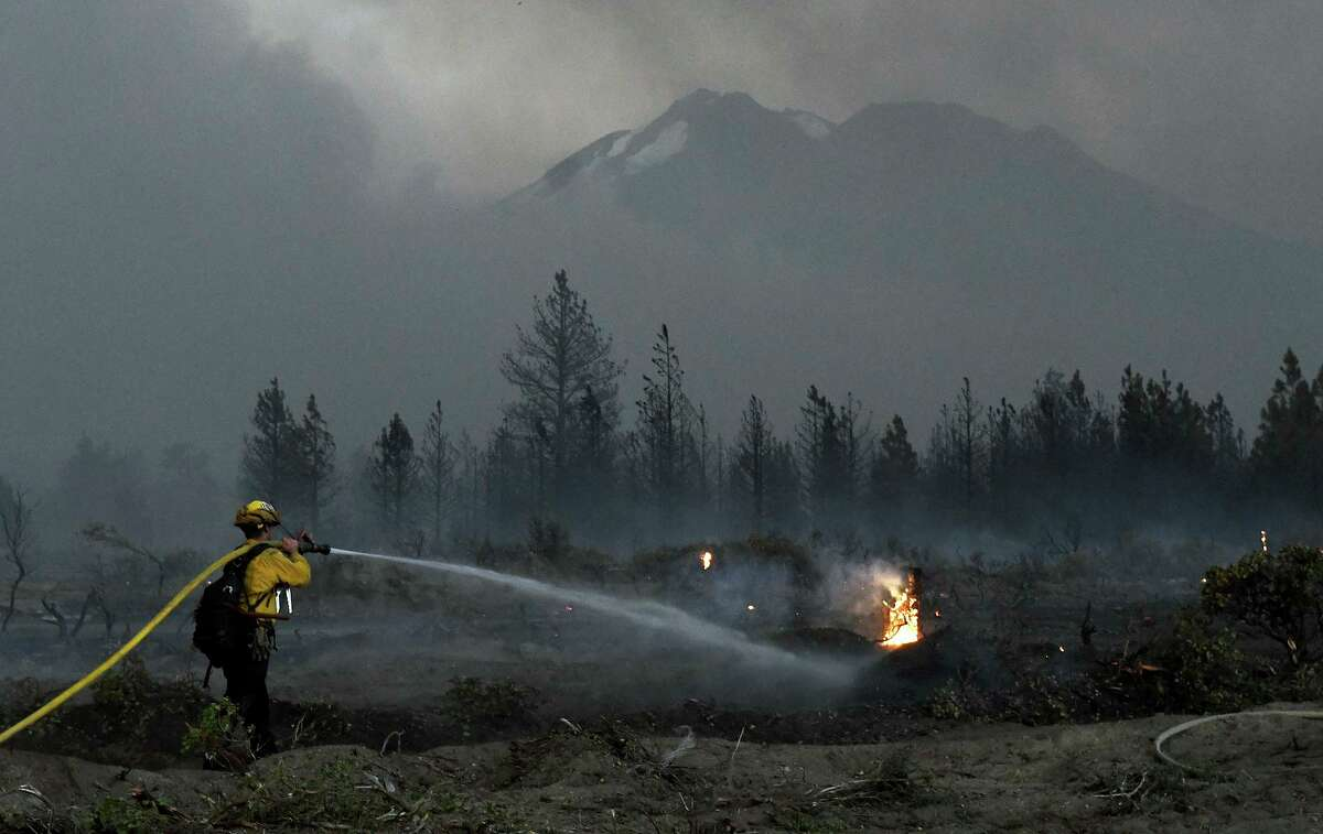 With Mount Shasta in the background, a firefighter cools down hot spots of the Lava Fire on Monday north of Weed.