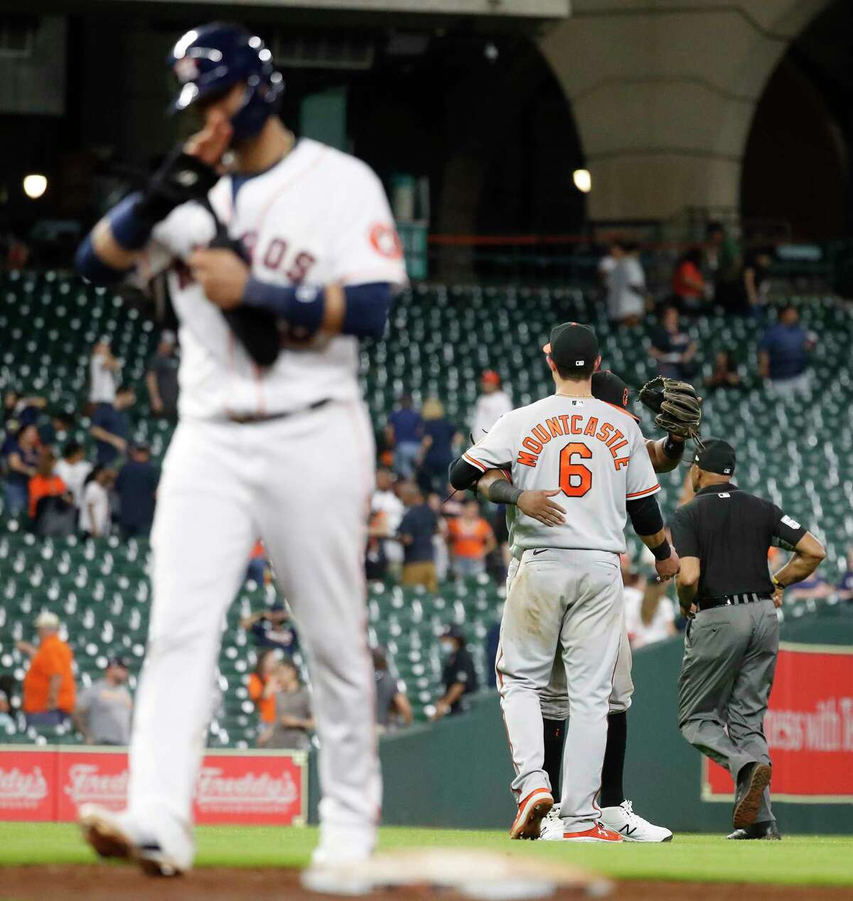 Baltimore Orioles Maikel Franco (3) hugsRyan Mountcastle (6) as Houston Astros Yuli Gurriel (10) walked back to the dugout after the Orioles beat the Houston Astros 13-3 during an MLB baseball game at Minute Maid Park, Tuesday, June 29, 2021, in Houston.