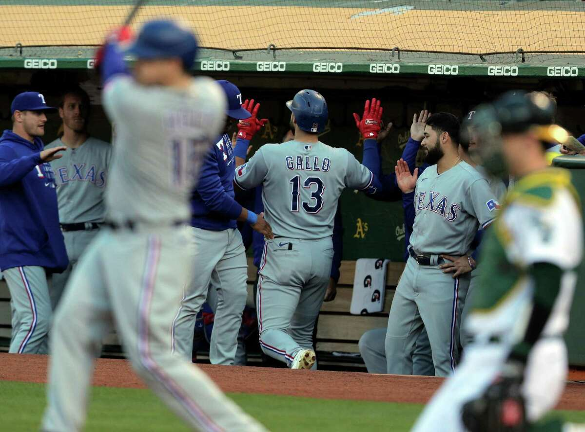 Joey Gallo (13) congratulated by teammates after hitting his first solo homerun of the game in the fourth inning as the Oakland Athletics played the Texas Rangers at the Coliseum in Oakland, Calif., on Tuesday, June 29, 2021.