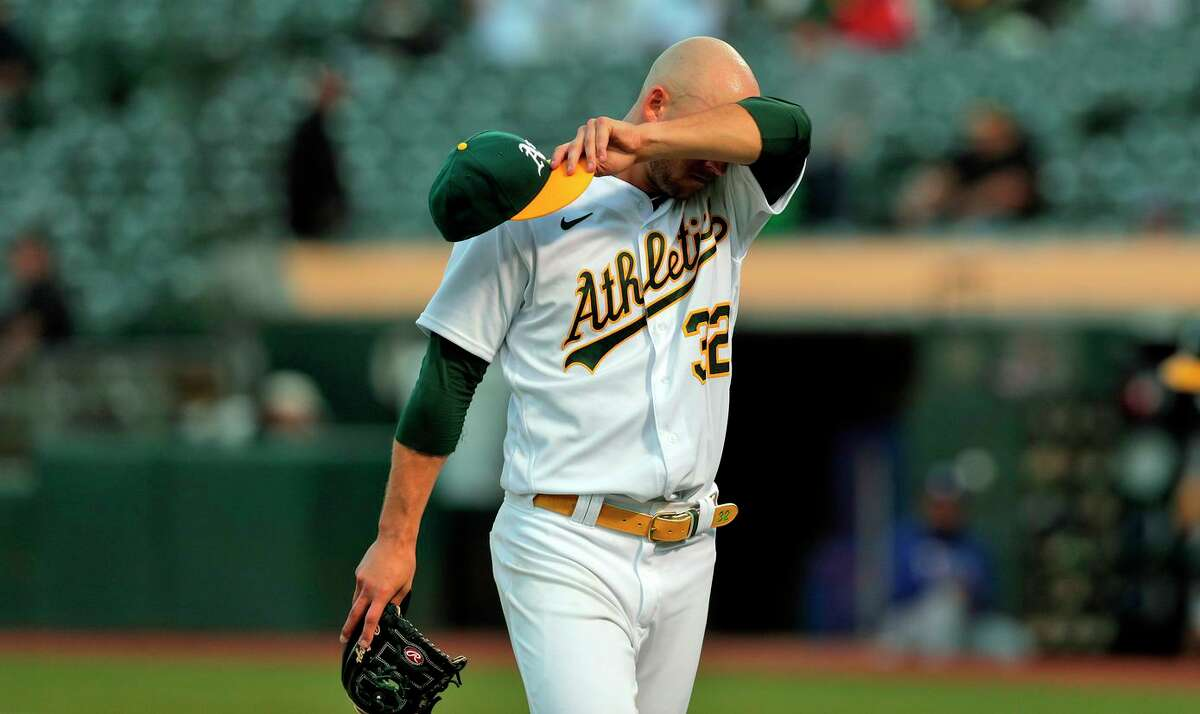 James Kaprielian (32) wipes his brow after finishing the fifth inning and giving up the lead earlier on a Joey Gallo (13) solo homerun as the Oakland Athletics played the Texas Rangers at the Coliseum in Oakland, Calif., on Tuesday, June 29, 2021.