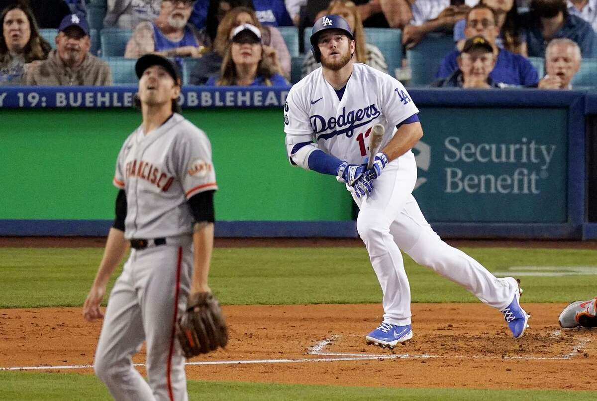 Los Angeles Dodgers' Max Muncy, right, runs to first as he hits a solo home run while San Francisco Giants starting pitcher Kevin Gausman watches during the third inning of a baseball game Tuesday, June 29, 2021, in Los Angeles. (AP Photo/Mark J. Terrill)