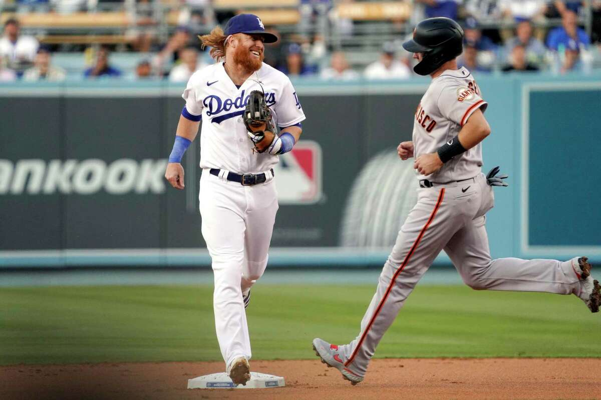 Los Angeles Dodgers third baseman Justin Turner, left, smiles at San Francisco Giants' Buster Posey as he forces him out at second to end the top of the first inning of a baseball game Tuesday, June 29, 2021, in Los Angeles. (AP Photo/Mark J. Terrill)