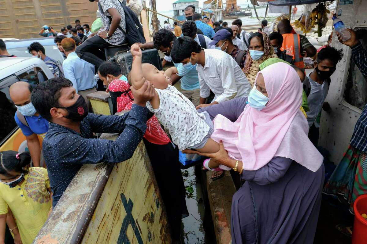 A child is handed over to board a ferry as people crowd a ferry terminal to leave the city ahead of a lockdown set to start on July 1, in Munshiganj, on the outskirts of Dhaka, Bangladesh, Wednesday, June 30, 2021.