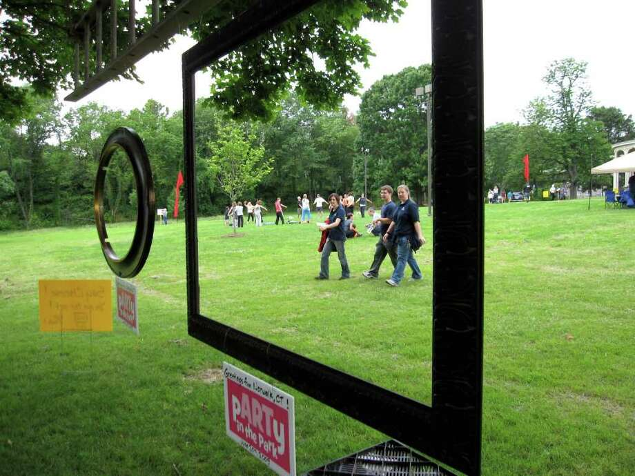 Jackie Lightfield, chairwoman of the Norwalk Arts Commission, uses her camera to capture a few of last year's pARTy in the Park attendees as they wander near an outdoor sculpture. This year, Norwalk will celebrate a citywide celebration of the arts with the daylong 'Norwalk Arts: Inside/Out,' on Sept. 25, which encourages visitors to visit open studios, galleries and other sites. Photo: Contributed Photo / Stamford Advocate Contributed