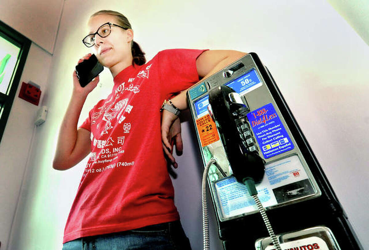 In this photo illustration, a resident uses a modern-day cellphone while resting on a payphone located in the Edwardsville Public Library. The Intelligencer set out to find the number of payphones that stand within the city of Edwardsville. However, finding an official answer was not a simple task.