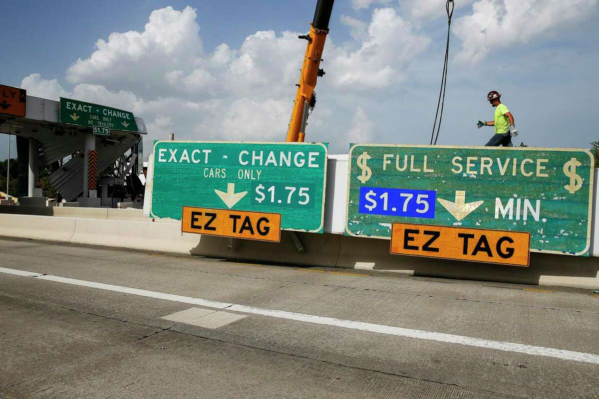 A contractor walks along part of a toll plaza on the Hardy Toll Road on July 15, 2016 in Houston as crews demolish the structure. The road was closed in preparation of reopening as an all-electronic toll road.