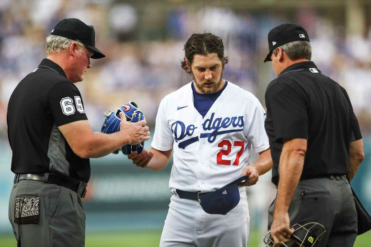 Umpires check the hat and glove of Trevor Bauer of the Los Angeles Dodgers for foreign substances after the first inning against the San Francisco Giants at Dodger Stadium on June 28, 2021 in Los Angeles, California.