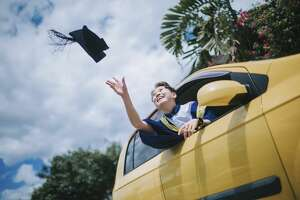 young female with graduation robe throwing cap in the air from driver seat of her car laughing